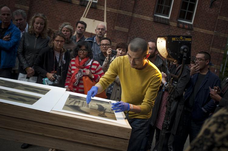 Photographer Daisuke Yokota in a book performance at Amsterdam's UNSEEN photo fair, in 2014.