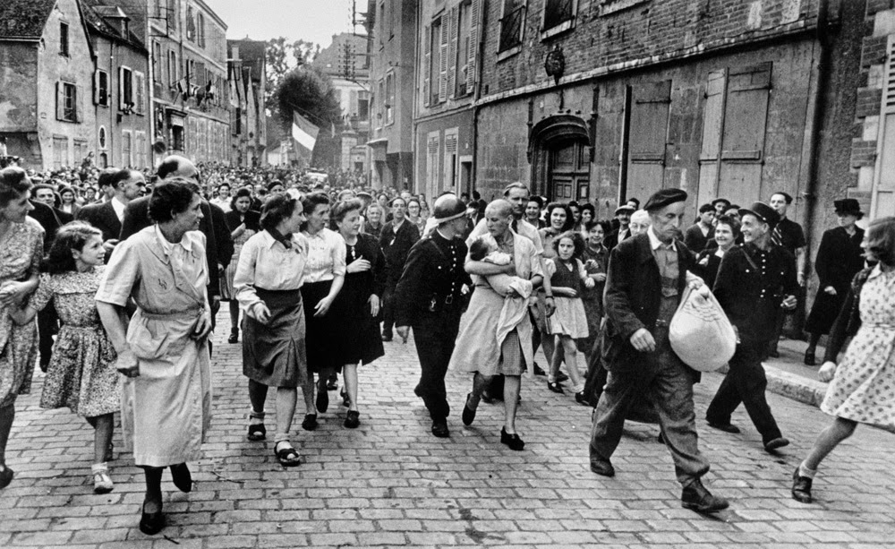 Simone Touseau, a French collaborator, being marched through the streets of Chartres prior to the liberation of France by the Allies.